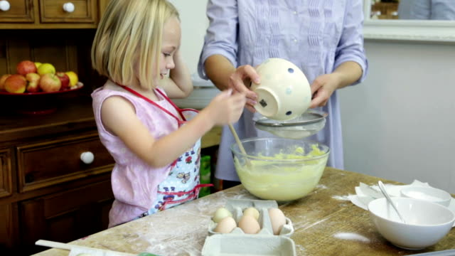 Baking... Tracking shot of a young girl helping out in the kitchen... recipe stock videos & royalty-free footage