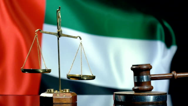 balance and gavel with united arab emirates flag - cartello economico video stock e b–roll
