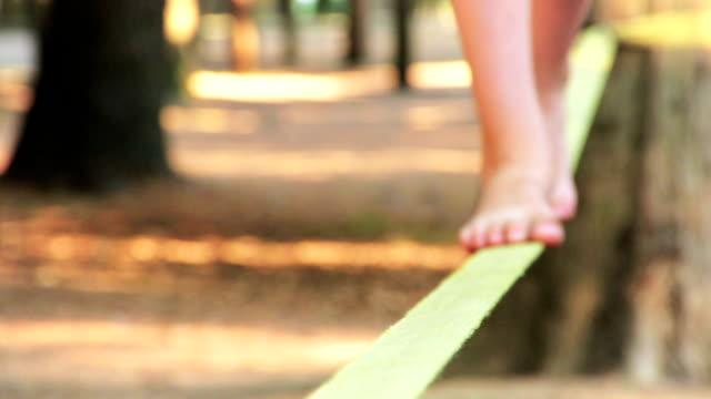 bilanciamento a piedi nudi su un slackline - balance video stock e b–roll