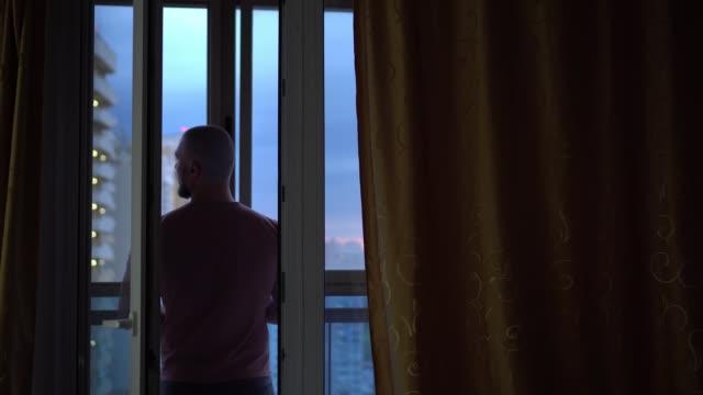 vídeos de stock, filmes e b-roll de um careca fica perto da janela aberta e olha para a cidade. fora do edifício vários andares. o conceito de liberdade e prazer. - característica arquitetônica