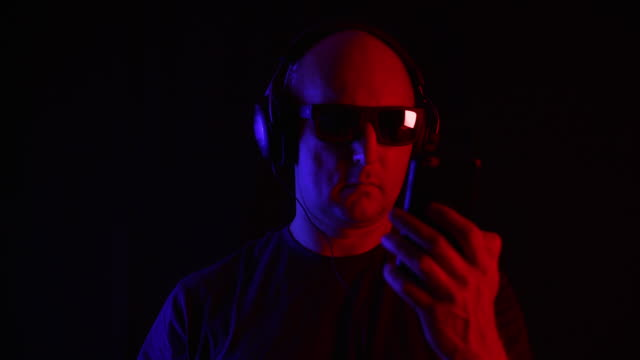 Bald man using smartphone and listening music in headphones in studio - vídeo