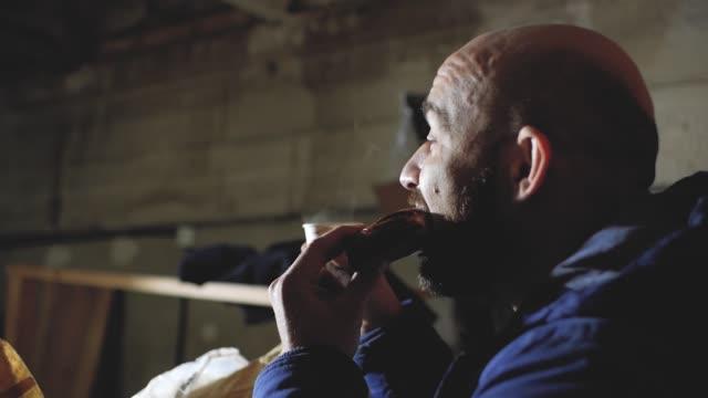 stockvideo's en b-roll-footage met kale man met een baard eet een brood en drinkt koffie - camelia white