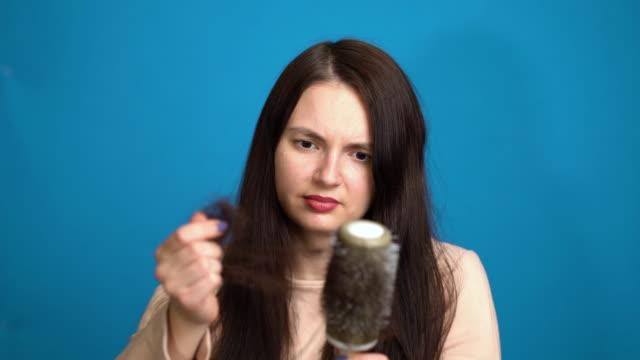 はげの問題の女性。女の子の手は損失の毛の櫛を保持しています。 ビデオ