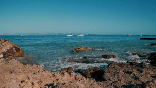 Balearic Island Formentera Rocky Beach Spain Balearic island Ibiza Formentera , sunny summer day , sea waves washing the shores of a beach , big rock on the shore yachting stock videos & royalty-free footage