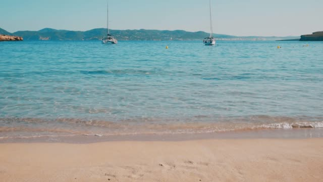 Balearic Island Ibiza Cala Bassa Beach in the Summer Spain Balearic island Ibiza Cala Bassa beach , sunny summer day , blue sea , mountain island in the background , blue sky , sailing boat , clean beach yachting stock videos & royalty-free footage