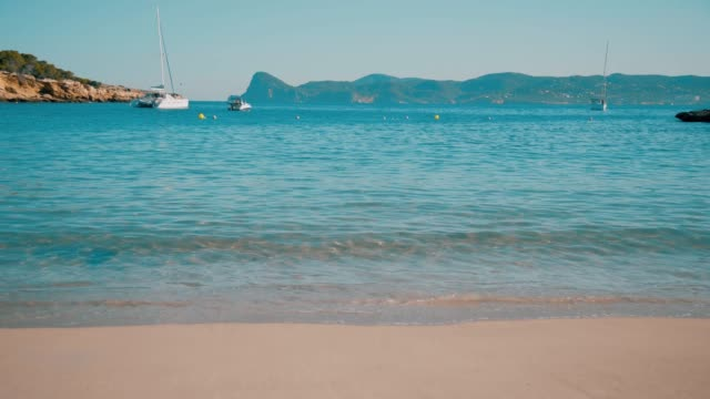 Balearic Island Ibiza Cala Bassa Beach Spain Balearic island Ibiza Formentera , sunny summer day , blue sea , mountain island in the background , blue sky , sailing boat , clean beach yachting stock videos & royalty-free footage