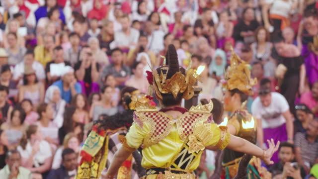 bali, indonesien-26.06.2018-orientaliska religiösa danser, där det finns en man med en mask och färgglada kostymer dansar framför sin befolkning. - sarong bildbanksvideor och videomaterial från bakom kulisserna