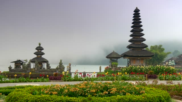 Bali, Indonesia. Pura Ulun Danu Bratan Temple surrounded by beautiful flowers with mist covered water in the background. Pura Bratan is a water temple of shaivism (worship Shiva). 4K video