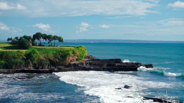 vídeos de stock, filmes e b-roll de paisagem de bali com as ondas do oceano e saliência rochosa com árvores - arméria