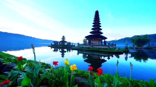Bali Pura Ulun Danu Bratan Temple, silhouette and sunset sunshine over holy site in Indonesia,shot by crane video