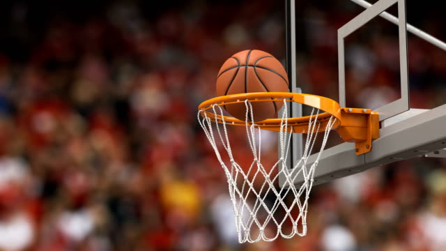 Ball Flies Spinning into Basketball Hoop Tribunes Background. Beautiful Basketball Ball Hits Basket Net Slow Motion Close-up. Sport Concept. 3d Animation 4k UHD 3840x2160.