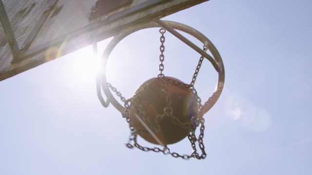 Ball passing through basketball hoop on sunny day