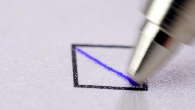 Ball pen putting crosses in tick box.