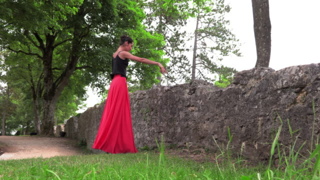 Ballerina dancing near the ruins of an old castle