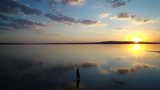 vidéos et rushes de ballerine, danse sur le lac au coucher du soleil. antenne prise - lac salé