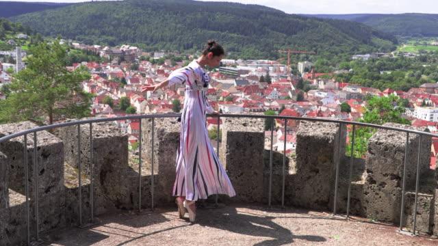 ballerina dansar på gatan på ruinerna av ett gammalt slott - på tå bildbanksvideor och videomaterial från bakom kulisserna
