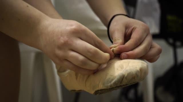 a ballerina girl fastens her shoe before the show - scarpe video stock e b–roll