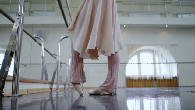 ballerina i balett skor pointe sträcker på barre i gymmet. slow motion. kvinna som tränar i dansstudio. arbeta ur ung flicka i beige kostym. naturligt ljus - piruett bildbanksvideor och videomaterial från bakom kulisserna