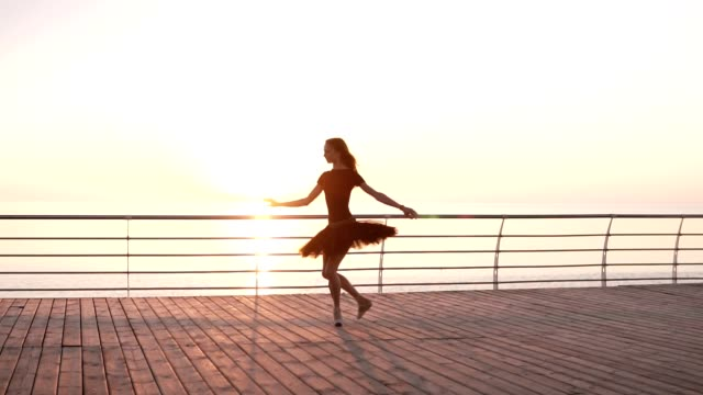 Ballerina in black ballet tutu and point on embankment above ocean or sea at sunrise. Jumping ballerina, practicing classic exercises. Slow motion video