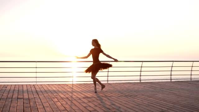 バレリーナ ブラック バレエ チュチュと海や日の出海上堤防上のポイント。古典的な演習を実施、バレリーナをジャンプします。スローモーション - バレリーナ点の映像素材/bロール