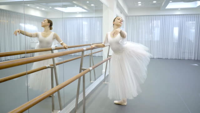 Ballerina in tutu and pointe is engaged near ballet machine video