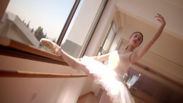 Ballerina in tutu skirt practising her techniques on a barre video