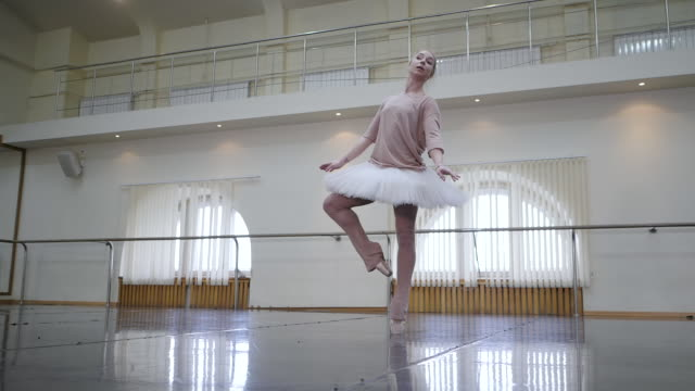 ballerina aus weißem ballett tutu kleid üben im tanzstudio oder fitness-studio. frau tanzt klassische pas in der klasse. allein aufwärmen vor leistung. erstaunliche tanz. slow-motion - ballettschuh stock-videos und b-roll-filmmaterial