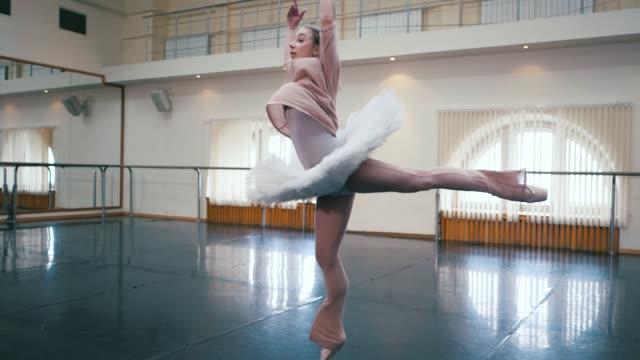 ballerina i vitt balett tutu klänning öva i dansstudio eller på gymmet. kvinna hoppa i klassrummet. enbart värma upp före föreställningen. fantastiska dans. slow motion - balettstång bildbanksvideor och videomaterial från bakom kulisserna