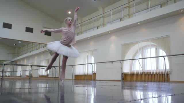 ballerina i vitt balett tutu klänning öva i dansstudio eller på gymmet. kvinna dans klassiskt pas i klass. enbart värma upp före föreställningen. fantastiska dans. slow motion - piruett bildbanksvideor och videomaterial från bakom kulisserna