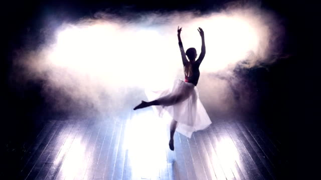 A ballerina jumps through a dark wooden stage. video