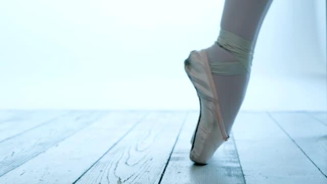 ballerina kneads her feet in pointe shoes on the wooden floor - scarpette per danza classica video stock e b–roll