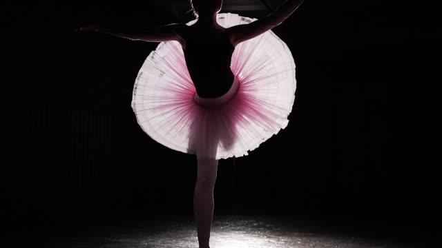 ballerina utför fouette varv i strålkastarljuset på svart bakgrund i träningsrummet. kvinnliga balettdansös tutu och pointe skor. slow motion. - piruett bildbanksvideor och videomaterial från bakom kulisserna