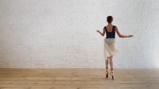 ballerina utför pirouette i rum på tegel vägg bakgrunden - piruett bildbanksvideor och videomaterial från bakom kulisserna
