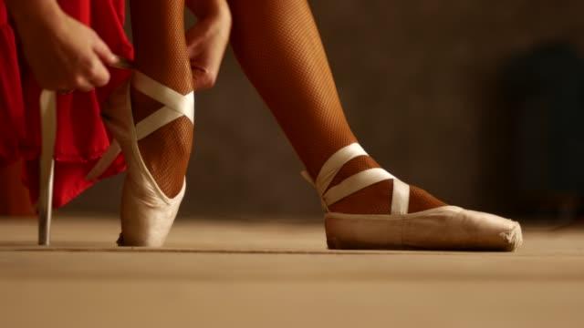 ballerina setzt spitzenschuhe an. vorbereitungaufdie auf die bühne. hintergrundbeleuchtung, schönes kleid - ballettschuh stock-videos und b-roll-filmmaterial