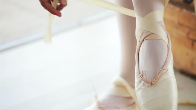 ballerina putting auf ihre schuhe - ballettschuh stock-videos und b-roll-filmmaterial