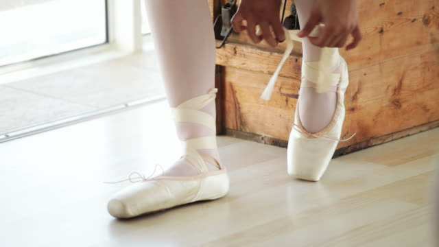 Ballerina putting on her shoes Modern day ballerina practicing in her apartment, tying up her ribboned shoes. dress shoe stock videos & royalty-free footage