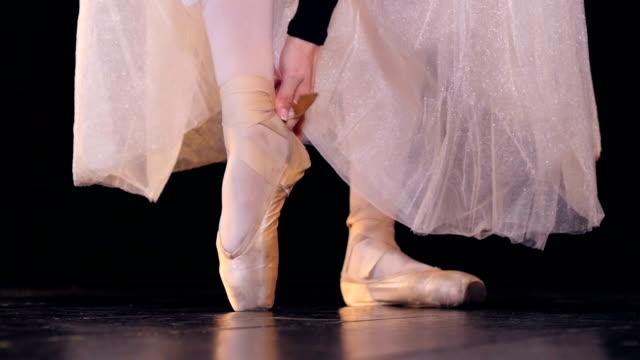 vídeos de stock e filmes b-roll de a ballerina straps her ballet shoes laces on her ankle. - tule têxtil