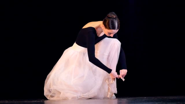 a ballerina ties up her white shoe. - tutù video stock e b–roll