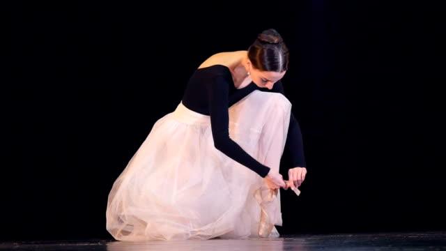 eine ballerina fesselt ihre weißen schuh. - ballettschuh stock-videos und b-roll-filmmaterial