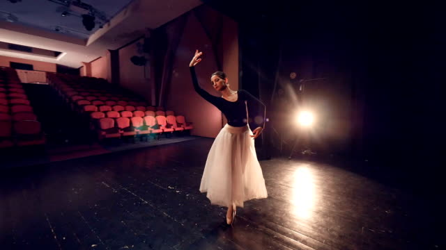 A ballerina turns around in the center of an empty stage. video
