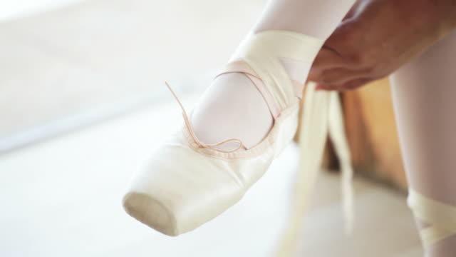 ballerina binden sie eine schleife auf ihr ballett-schuh - ballettschuh stock-videos und b-roll-filmmaterial