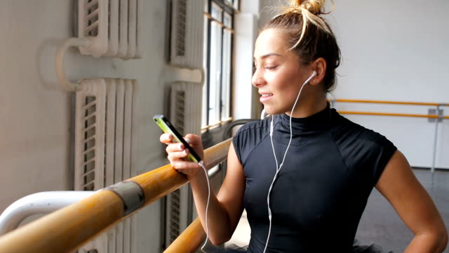 en ballerina använder en smartphone i en stor träningshall - balettstång bildbanksvideor och videomaterial från bakom kulisserna