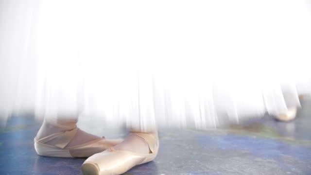 vídeos de stock e filmes b-roll de ballerinas in white tutus bounce up on pointe shoes in a studio - tule têxtil