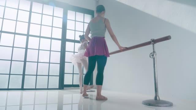 Ballet coach and her cute ballerina girl with ballet dancing class
