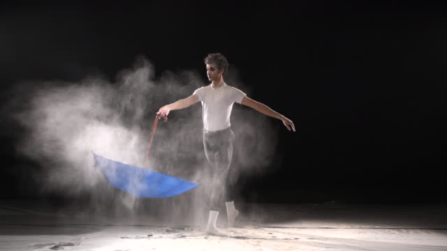 Ballet Dancer dancing with powder snow and umbrella at studio. Slow motion video