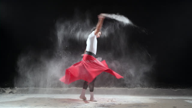 Ballet Dancer dancing with powder snow at studio. Slow motion video