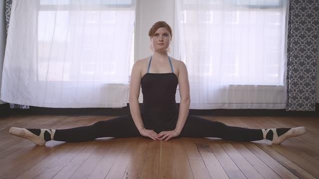 ballett-tänzerin den spagat in einem studio zu tun - gymnastikanzug stock-videos und b-roll-filmmaterial
