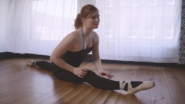ballett-tänzerin senken sich in die splits in einem studio - gymnastikanzug stock-videos und b-roll-filmmaterial