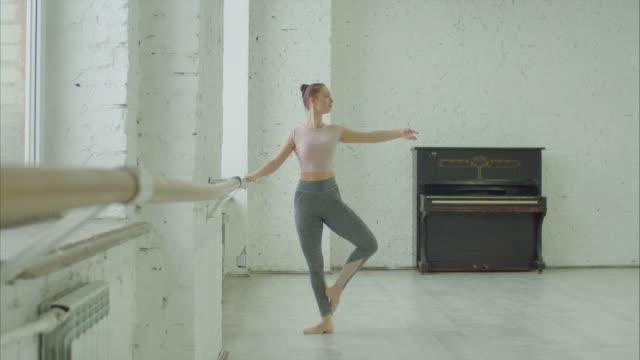 balettdansare utför dedans motion på barre - balettstång bildbanksvideor och videomaterial från bakom kulisserna