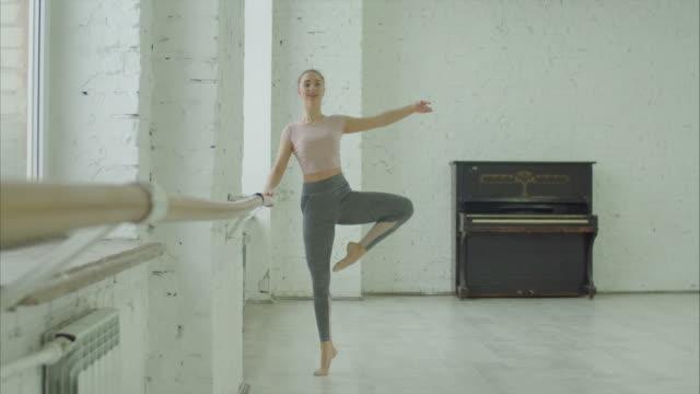 balettdansare utför dehors motion på barre - balettstång bildbanksvideor och videomaterial från bakom kulisserna